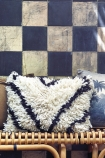 lifestyle image of Black & White Wool Cushion on rattan bench with blue and white check wallpaper background