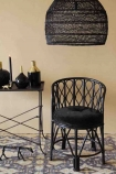 lifestyle image of Black Bamboo Chair With Velvet Seat Pad with Giant Black Wicker Dome Ceiling Light and black console table on patterned rug and cloisters painted wall bckground