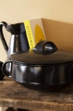 Lifestyle image of the Black Brown Terracotta Casserole Dish - Large on crowded wooden shelf with pale wall background
