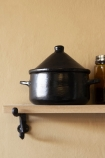Lifestyle image of the Black Brown Terracotta Small Casserole Tagine Dish on Oak Shelf With Cast Iron Brackets - Small with pale wall background