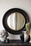 lifestyle image of Black Convex Mirror With Aged Gold Detail with Blind Faith Stone Effect Head, black and white vase and candle on black table with pale wall background