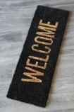 lifestyle image of Black & Gold Welcome Doormat on wooden flooring