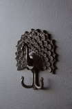 lifestyle image of Black Peacock Wall Hook on dark grey wall