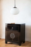 Angled lifestyle image of the Oriental Gloss Black Bedside Table