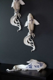 Lifestyle image of three White & Blue Oriental Koi Karp Fish Wall Decoration with 2 on the wall and one on a shelf facing right