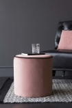 lifestyle image of Blush Pink Pouffe With Black Piping on grey rug with glass on top and black leather chair with pink cushion on top in background and dark grey wall background