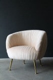 Lifestyle image of the Blush Pleated Velvet Tub Armchair on grey flooring and dark wall background