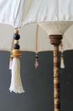 detail image of tassels on Boho Beaded Cotton Garden Umbrella with dark wall background