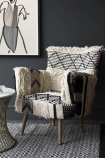 lifestyle image of shaggy Boho Woven Armchair on black and white rug with side table on dark grey wall background and art print on wall