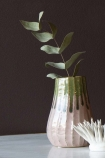Lifestyle image of the Botanical Bottle Neck Vase on marble table with plant inside and coral ornament with dark wall background