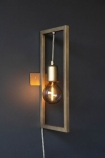 Lifestyle of Brass Effect Hanging Lamp In Frame fixed to dark grey wall wall bulb on