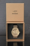 Leff Amsterdam Brass Tube Watch With Links By Piet Hein Eek in brown box on grey background lifestyle image