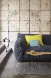 lifestyle image of NLXL TIN-03 Brooklyn Tin Tiles Wallpaper By Merci with grey sofa with yellow and blue cushions and wooden coffee table