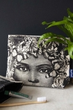 lifestyle image of Butterfly Lady Wash Bag  Make-Up Bag with bathroom accessories and plant on grey surface and dark blue wall background