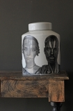 White ceramic jar in a fornasetti style with faces on it on wooden shelf with dark wall background lifestyle image