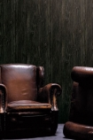 lifestyle image of Koziel Charred Wood Boarding Wallpaper with brown leather armchairs