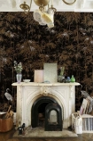 Lifestyle image of the Chinoiserie Wallpaper Mural - Garzas Coal with white fireplace with ornaments on mantelpiuece with chandelier with boots hanging from it and baskets on floor