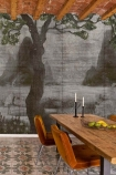 Lifestyle image of the Chinoiserie Wallpaper Mural - Zilant Chai Seed with long woode dining table with burnt orange dining chairs and wooden beam ceiling with patterned tile flooring