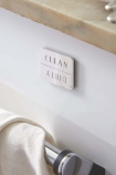 lifestyle image of Clean Dirty Dishwasher Indicator Magnet - Brass Or Stainless Steel Available on white wall under windowsill and above silver towel rail with towel on