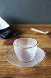 lifestyle image of Clear Glass Cup & Saucer on wooden table with gold spoon and bag of coffee