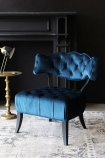lifestyle image of Cloud Velvet Chair - Midnight Blue with gold side table and table lamp on patterned grey rug and black wall background