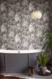lifestyle image of Cole & Son - The Ardmore Collection - Savuti in bathroom with large grey and white bath, white ceiling light and house plants with rug on floor