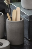 lifestyle image of Concrete Toothbrush Mug with wooden sticks in on crowded black tabletop