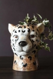 Lifestyle image of the Cute Cheetah Vase with trailing ivy in it on dark wooden surface and dark wall background