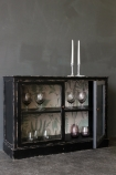 detail image of Distressed Black Display Cabinet With Botanical Lining with door open with glasses inside and candlesticks on top on dark grey wall background