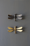 lifestyle image of Antique Black Dragonfly Hook and Brass Dragonfly Hook on black wall background