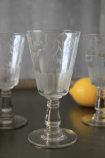 lifestyle image of Etched Wine Glass with two other glasses and lemon on black table and grey wall background