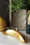 lifestyle image of Fabulous Gold Banana Candle with  gold lemon candle and plant on marble table