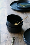lifestyle image of Faria Black Bowl with gold spoon and other crockery on wooden table