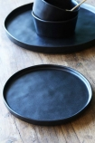 lifestyle image of Faria Black Dinner Plate with other black crockery on wooden table
