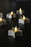 lifestyle image of Glitter Star Tea Lights - Gold lit up on black table