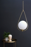 lifestyle image of Globe Pearl Drop Ceiling Light with gold tray side table with plant and bust ornament with dark wall background