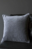 lifestyle image of Glorious Velvet Cushion - Slate Grey on black chair with grey wall background