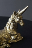 detail image of Gold Glitter Unicorn Ornament on black table with grey wall background