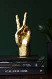 lifestyle image of Gold Peace Hand Ornament on pile of books with dark green wall background