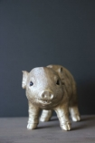 lifestyle image of Gold Piggy Coin Bank on grey table with grey wall background