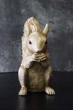 lifestyle image of Gold Squirrel Coin Bank from front on black table and distressed grey wall background