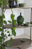 Close-up lifestyle image of the Three-Tier Brass Shelving Unit with faux plants drapping