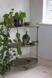 Lifestyle image of the Three-Tier Brass Shelving Unit with faux plants drapping