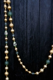 Zoomed out image of the Gold & Green Glass Garland