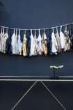 lifestyle image of Black & Gold Tassel Garland over gold console table and dark wall background