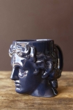 Side-on lifestyle image of the Greek Goddess Hestia Mug in blue on wooden surface and brown painted wall background