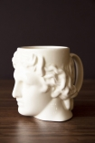 Side-on lifestyle image of the Greek Goddess Hestia Mug in white on dark wooden surface and dark wall background