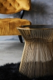 close up lifestyle image of Hampstead Gold Side Table with Cloud Velvet Chair - Golden Glow behind and black sheepskin with distressed grey wall background