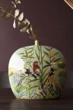Lifestyle image of the Hand Painted Jungle Deco Vase with gold eucalyptus inside on dark purple wall background