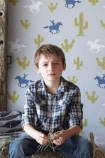 lifestyle image of Hibou Home Cactus Cowboy Children's Wallpaper with little boy wearing tartan shirt in front